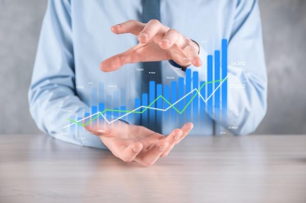Geschäftsmannmann, der eine grafik mit positivem gewinnwachstum hält. planen sie das wachstum des diagramms und die erhöhung der positiven indikatoren des diagramms in seinem geschäft. profitabler und wachsender.