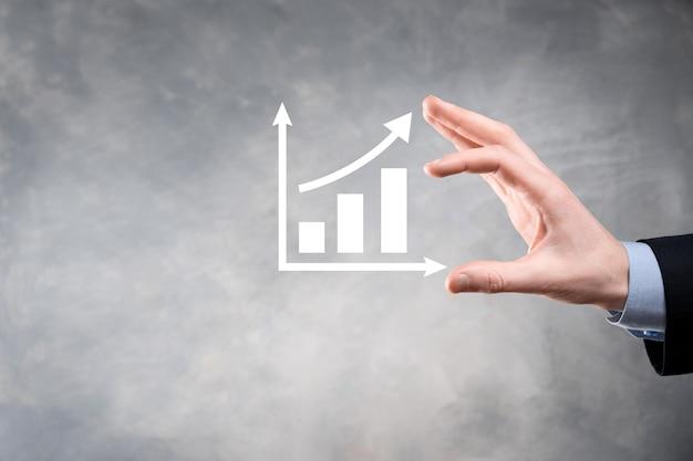 Geschäftsmannmann, der eine grafik mit positivem gewinnwachstum hält. planen sie das wachstum des diagramms und die erhöhung der positiven indikatoren des diagramms in seinem geschäft.