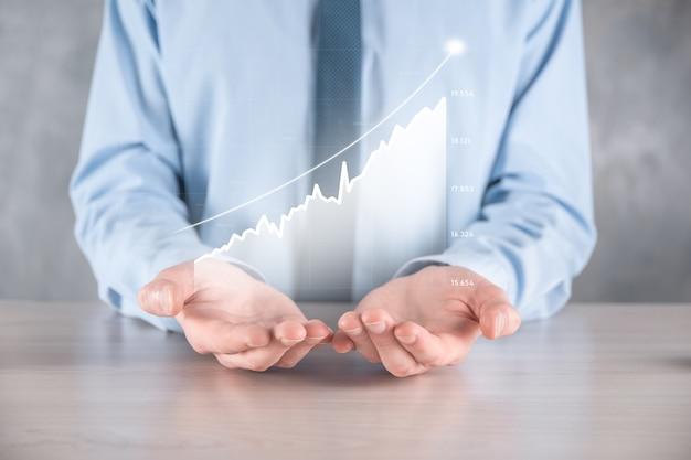 Geschäftsmannmann, der eine grafik mit positivem gewinnwachstum hält. planen sie das wachstum des diagramms und die erhöhung der positiven indikatoren des diagramms