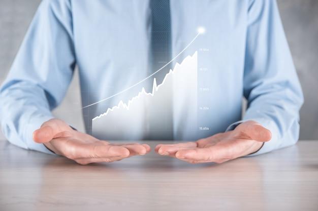 Geschäftsmannmann, der eine grafik mit positivem gewinnwachstum hält