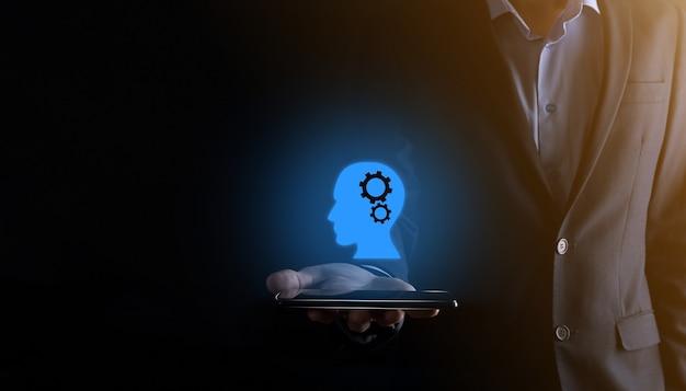 Geschäftsmannmann, der eine mannikone mit zahnrädern in seinem kopf hält. künstliche intelligenz. technologische fortschritte. roboter. kontursymbol.