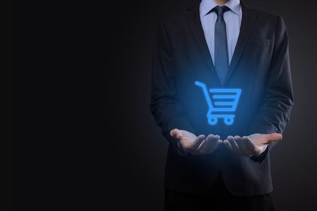 Geschäftsmannmann, der einkaufswagenwagen-mini-wagen in der digitalen zahlungsschnittstelle des geschäfts hält. geschäft, handel und einkaufskonzept.