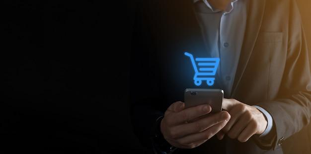Geschäftsmannmann, der einkaufswagenwagen-miniwagen in der digitalen zahlungsschnittstelle des geschäfts hält. geschäfts-, handels- und einkaufskonzept.