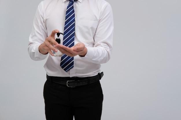 Geschäftsmannmann, der hand mit desinfektionsmittelspender für die desinfektion verhindert, die coronavirus verhindert
