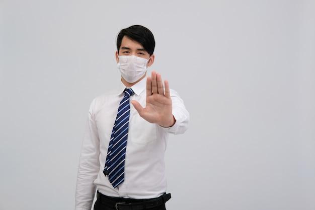 Geschäftsmannmann, der schutzmaske trägt und anhält