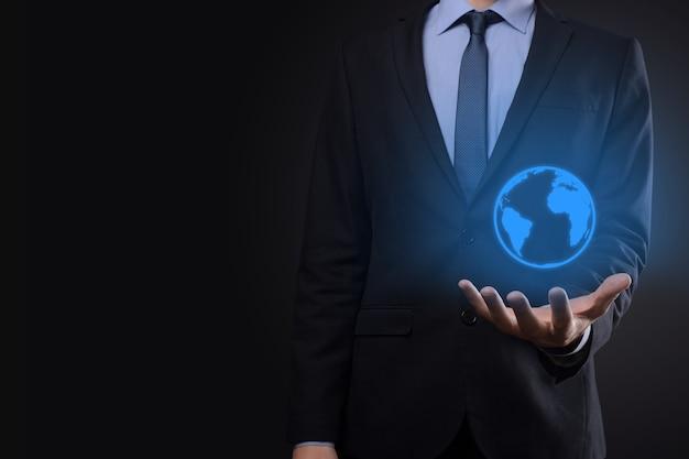 Geschäftsmannmannhand, die erdikone, digitale kugel hält