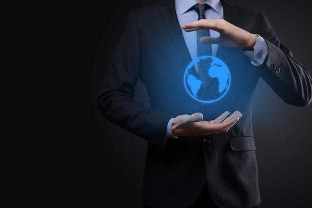 Geschäftsmannmannhand, die erdikone, digitaler globus hält