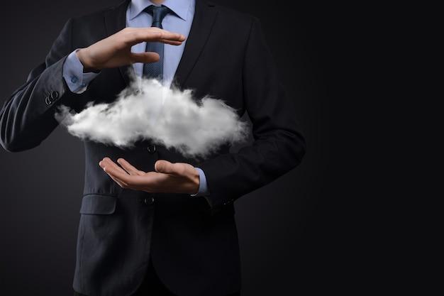 Geschäftsmannmannhand, die wolke hält. cloud-computing-konzept, nahaufnahme des jungen geschäftsmannes mit wolke über seiner hand. das konzept des cloud-dienstes.