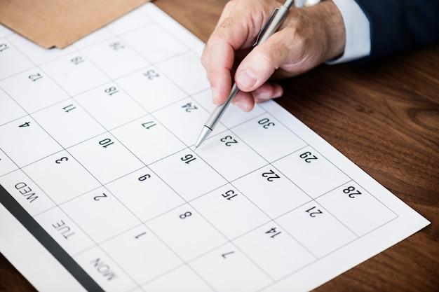Geschäftsmannmarkierung auf kalender für einen termin