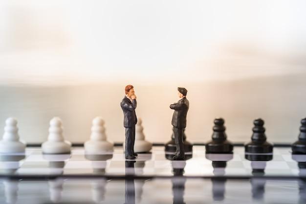 Geschäftsmannminiatur, die auf schachbrett mit schwarzweiss-schachfiguren steht