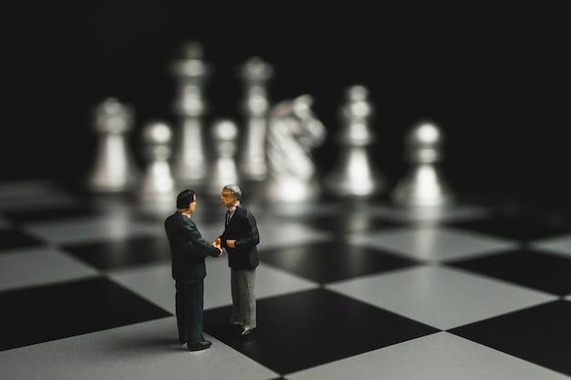Geschäftsmannminiaturhändedruck auf schachbrett mit silbernem schachhintergrund.