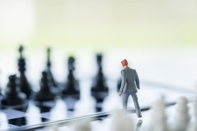 Geschäftsmannminiaturminizahlen, die auf schachbrett mit schachfiguren stehen und gehen