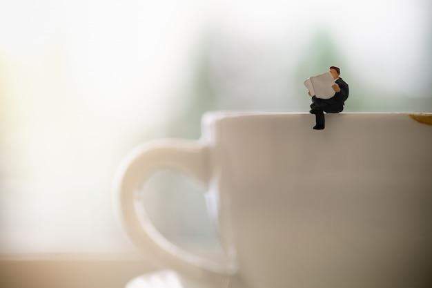 Geschäftsmannminiaturzahl, die eine zeitung auf schmutziger schale heißem kaffee mit kopienraum sitzt und liest.