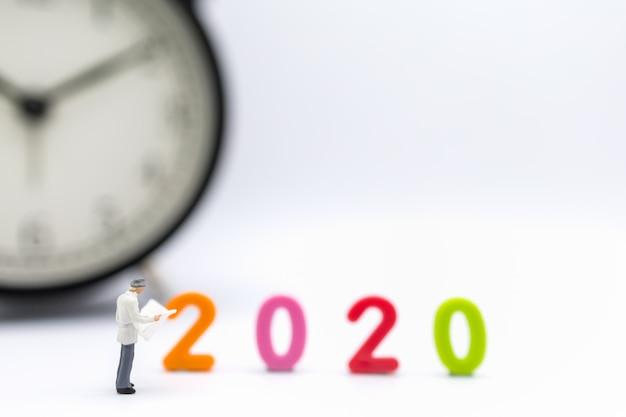 Geschäftsmannminiaturzahl, die eine zeitung mit 2020 bunter plastikzahl und uhr steht und liest