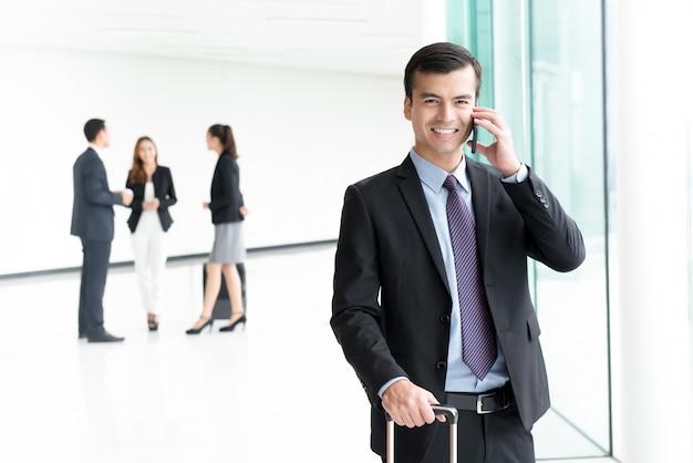 Geschäftsmannpassagier, der am handy anschließt an wi-fi am flughafen spricht