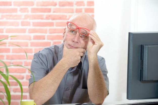 Geschäftsmannporträtälterer nachdenklich mit gläsern