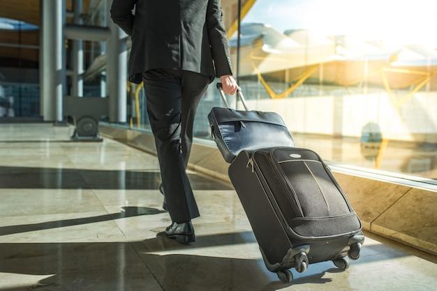 Geschäftsmannrücken und -beine, die mit gepäck am flughafen gehen