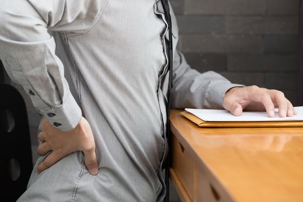 Geschäftsmannrückenschmerzen bei der arbeit, bürosyndromkonzept