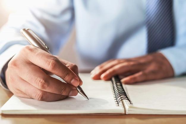 Geschäftsmannschreiben auf anmerkungsbuch im büro