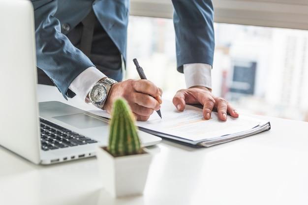 Geschäftsmannschreiben auf dokument mit stift auf schreibtisch mit laptop