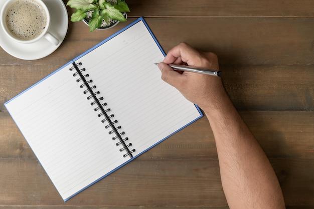 Geschäftsmannschreiben auf leerem notizbuch