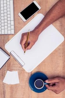 Geschäftsmannschreiben auf notizbuch am schreibtisch beim halten des kaffees im büro