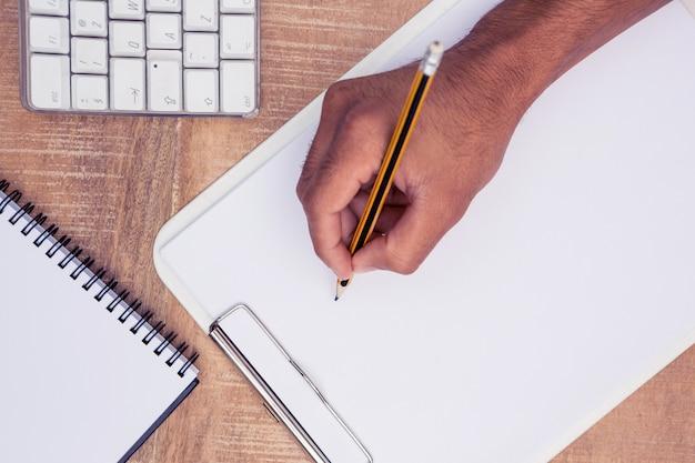 Geschäftsmannschreiben auf notizbuch am schreibtisch im büro