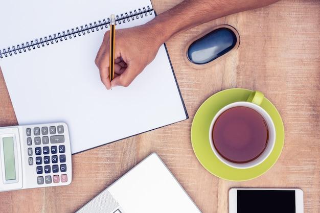 Geschäftsmannschreiben auf notizbuch durch kaffee am schreibtisch im büro