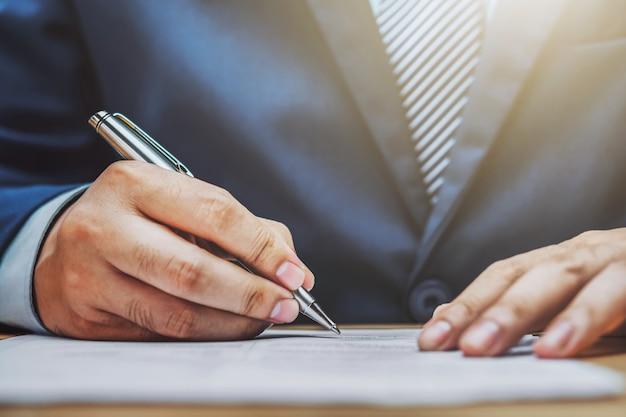 Geschäftsmannschreiben auf papierbericht im büro