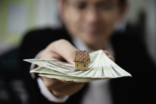 Geschäftsmannshow-geldbanknote lassen finanzplan leute einladen, haus und auto zu verkaufen oder zu kaufen - monetäre eigenschaften verleihen kreditversicherungskonzept