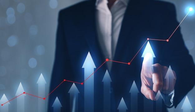 Geschäftsmannzeichnung auf dem bildschirm, der grafik wächst. geschäftsentwicklungskonzept.