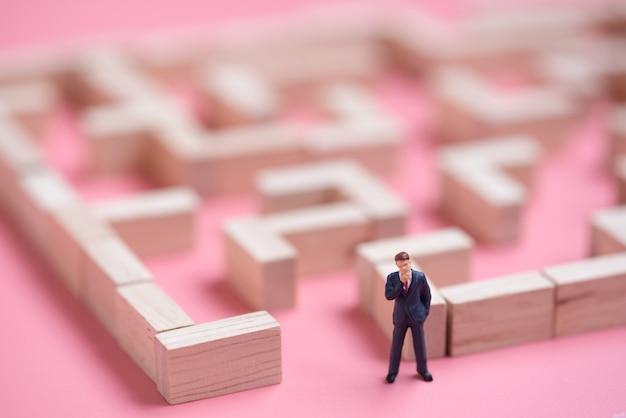 Geschäftsminiatur am anfangspunkt des puzzlespiellabyrinth-holzblocks