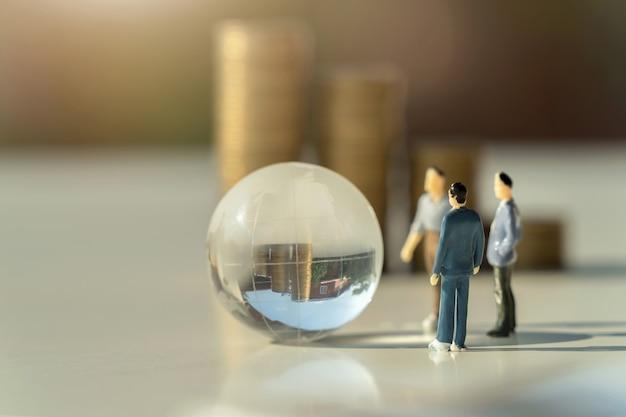 Geschäftsminiaturspielzeug mit globusglas auf weißer oberfläche
