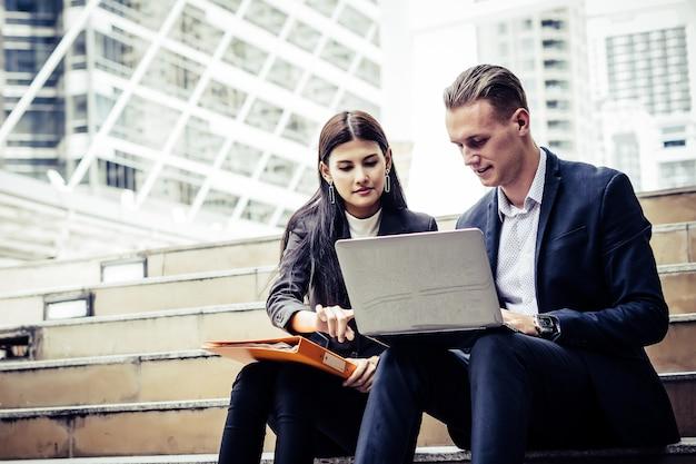 Geschäftsmitarbeiter, die neue ideen besprechen und auf dem laptop sitzend auf treppenhausbüro brainstorming sind