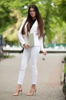 Geschäftsmobilitätskonzept mit einem porträt einer jungen geschäftsfrau im weißen anzug auf der bewegung um stadt mit einem laptop in der hand