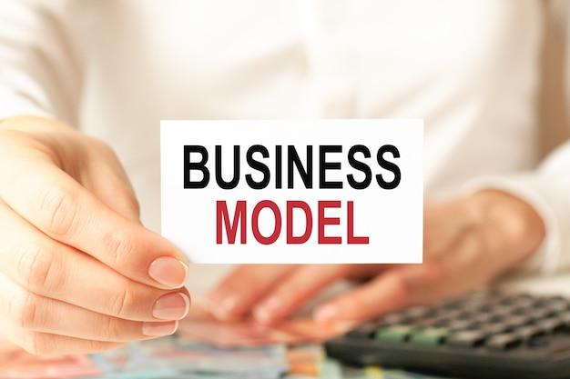 Geschäftsmodell steht auf einer weißen visitenkarte. die hand einer frau hält eine weiße papierkarte, weißer hintergrund. geschäfts- und werbekonzept. defokussieren.