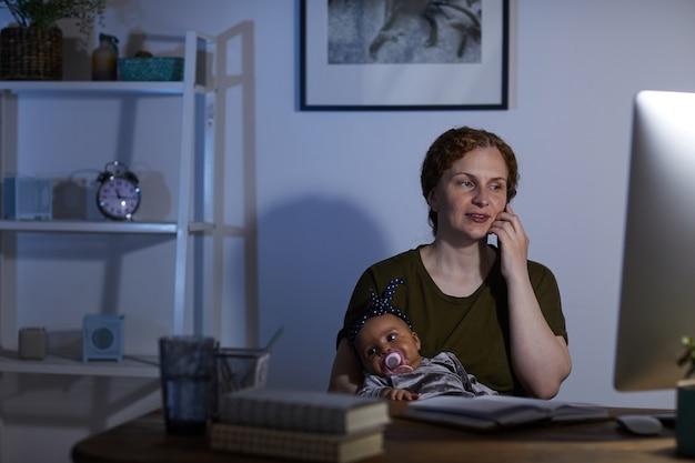 Geschäftsmutter, die computer benutzt und auf mobiltelefon spricht, während sie am tisch mit baby auf ihren knien sitzt