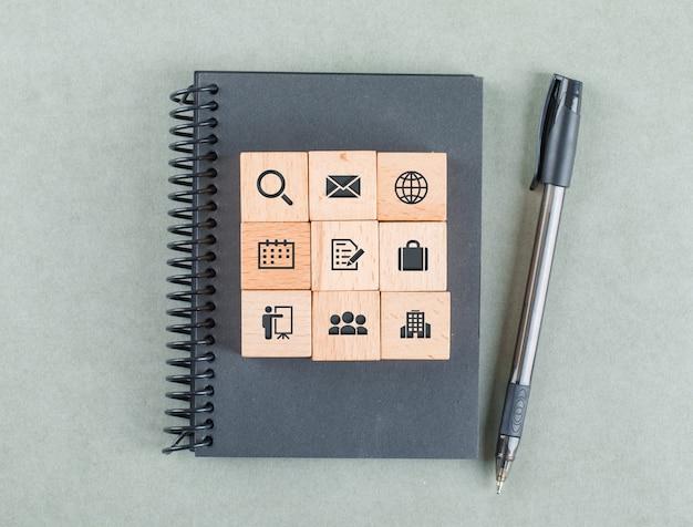 Geschäftsnotizkonzept mit holzklötzen mit ikonen, notizbuch, bleistift auf salbei-farbtisch-draufsicht.