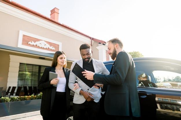 Geschäftspaar, afrikanischer mann und kaukasische frau, die draußen nahe dem schwarzen auto mit dem verkaufsmanager des jungen mannes stehen. familie kauft das auto. eleganter assistent, der den vertrag zeigt