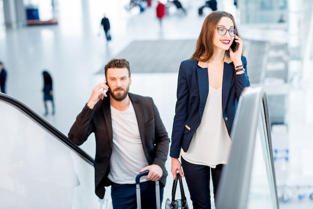 Geschäftspaar, das mit telefonen spricht, während es auf den rolltreppen mit gepäck am flughafen aufsteht?
