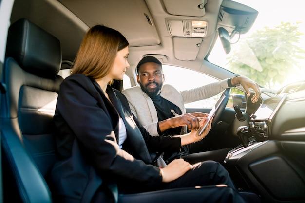 Geschäftspaar, hübsche kaukasische frau und schöner afrikanischer mann, im auto mit digitalem tablett arbeitend. mann zeigt etwas auf tablette für frau. business, finanzen, autoverkaufskonzept