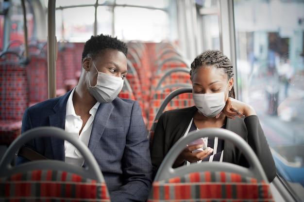 Geschäftspaar mit maske im bus, während es mit öffentlichen verkehrsmitteln in der neuen normalität unterwegs ist