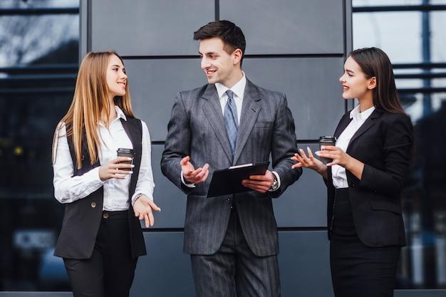 Geschäftspartner des bildes drei im schwarzen eleganten anzug sprechend und bei der diskussion der neuen strategie zusammenarbeitend