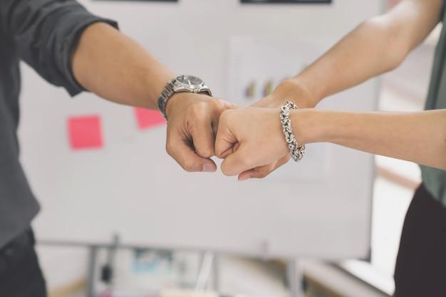 Geschäftspartner, die faust-bump geben, um mission erfolgreich abzuschließen, schließen zusammen ab