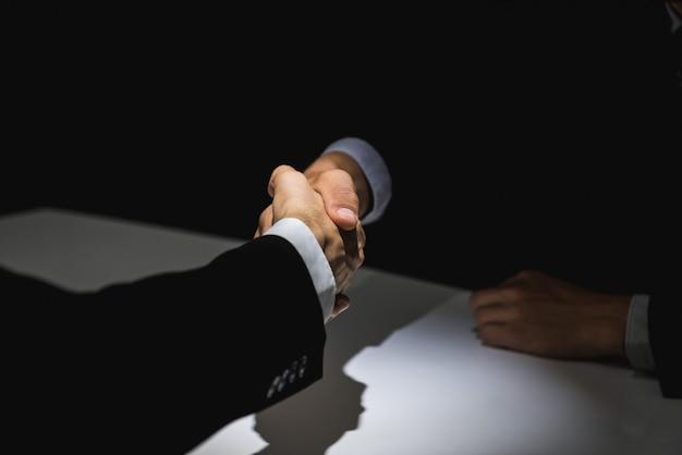Geschäftspartner, die händedruck im dunklen schatten machen