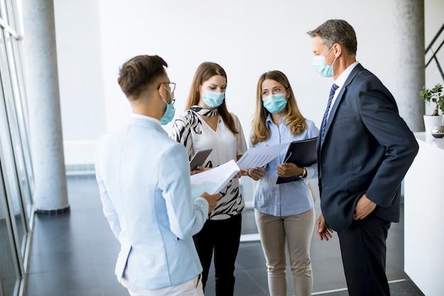 Geschäftspartner, die im büro stehen und geschäftsergebnisse betrachten, während sie gesichtsmasken tragen, sind ein virenschutz