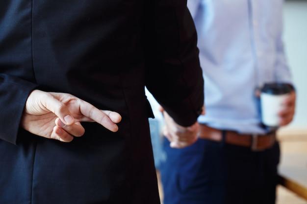 Geschäftspartner händeschütteln machen einen deal aber. geschäftsmann, der gekreuzte finger hinter dem rücken hält
