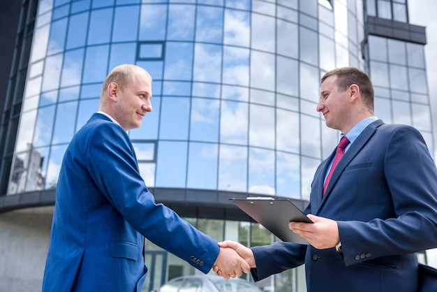 Geschäftspartner händeschütteln vor großem gebäude im freien