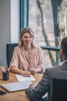 Geschäftspartner. junge freudige geschäftsfrau in heller bluse und mann im anzug mit seinem rücken zur kamera, die im büro kommuniziert