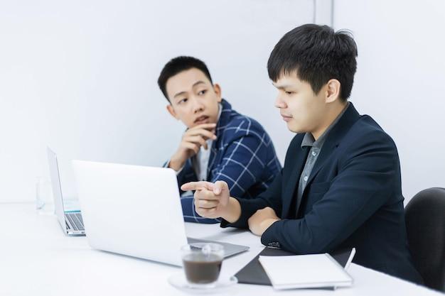 Geschäftspartner konzipieren einen jungen geschäftsmann, der mit seinem kollegen über einen marketingplan des neuen bevorstehenden produkts spricht.